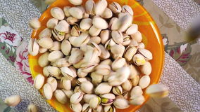 Pistachio nuts falling into bowl, slow motion stock video footage