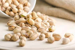 Pistachio nuts falling on a wooden board Royalty Free Stock Photo