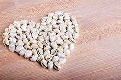Pistachio nuts forming a heart-shape on wooden floor background.  royalty free stock image