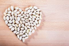 Pistachio nuts forming a heart-shape on wooden floor background.  royalty free stock photography