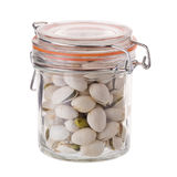 Pistachio nuts in a glass bottle isolated on a white background Royalty Free Stock Image