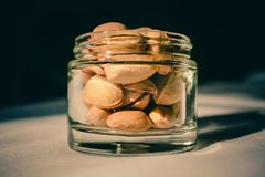Pistachio nuts in a glass container stock images
