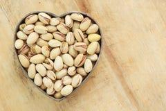 Pistachio nuts in heart shape Stock Photos