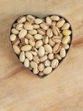 Pistachio nuts in heart shape Stock Photo