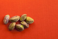 Pistachio nuts. On an orange background Royalty Free Stock Photography