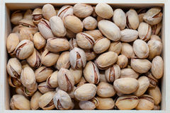 Pistachio nuts in a shell, salty, roasted in a wooden box Royalty Free Stock Photography