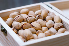 Pistachio nuts in a shell, salty, roasted in a wooden box Royalty Free Stock Photo