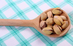 Pistachio nuts with spoon on checkered tablecloth, healthy eating Royalty Free Stock Images