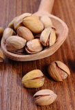 Pistachio nuts with spoon on wooden table, healthy eating Stock Image