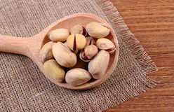 Pistachio nuts with spoon on wooden table, healthy eating Royalty Free Stock Photo