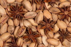 Pistachio nuts and star anise Macro. Light shell pistachios and juicy brown anise seeds Royalty Free Stock Photos