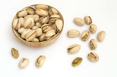 Pistachio nuts on white background in a bowl. Bowl full of pistachios, healthy and nutritious dried fruit, healthy fats stock photo