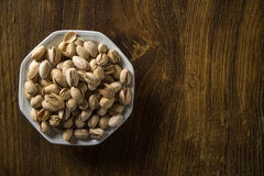 Pistachio nuts in white bowl with wood background. Royalty Free Stock Images