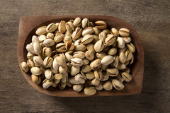 Pistachio nuts in wood bowl with wood background. Stock Photo