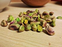 Pistachio nuts with wooden bowl in background royalty free stock photo