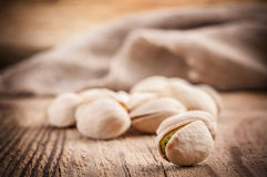 Pistachio nuts on wooden table Stock Photos
