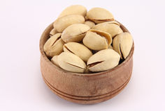 Pistachio in a round wooden form. On a white background Royalty Free Stock Image