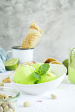 Pistachio sorbet with lime and mint. Homemade pistachio sorbet with lime, mint leaves, nuts and waffle cones. Selective focus stock images