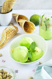 Pistachio sorbet with lime and mint. Homemade pistachio sorbet with lime, mint leaves, nuts and waffle cones. Selective focus stock photos