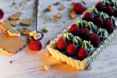Pistachio tart. Pistachio tart on white Belgian chocolate BARRY with a layer of raspberry confit, crispy shortbread base. Fading cream and juicy raspberries.A Royalty Free Stock Photo