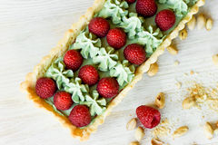 Pistachio tart. Pistachio tart on white Belgian chocolate BARRY with a layer of raspberry confit, crispy shortbread base. Fading cream and juicy raspberries.A Stock Photography