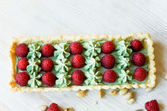 Pistachio tart. Pistachio tart on white Belgian chocolate BARRY with a layer of raspberry confit, crispy shortbread base. Fading cream and juicy raspberries.A Stock Photo