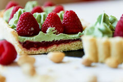 Pistachio tart. Pistachio tart on white Belgian chocolate BARRY with a layer of raspberry confit, crispy shortbread base. Fading cream and juicy raspberries.A Stock Photos