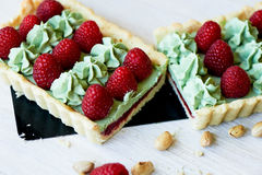 Pistachio tart. Pistachio tart on white Belgian chocolate BARRY with a layer of raspberry confit, crispy shortbread base. Fading cream and juicy raspberries.A Stock Image