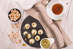 Pistachio truffles. Pistachio truffles with cream on wooden table stock photo