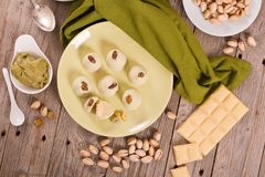 Pistachio truffles. Pistachio truffles with white chocolate on wooden table royalty free stock image