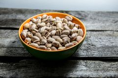 Pistachios in a bowl. On wooden background royalty free stock photo