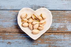Pistachios in a bowl shaped as a heart. Pistachios nuts snacks in a heart shaped plate on turquoise wooden background from above Royalty Free Stock Image