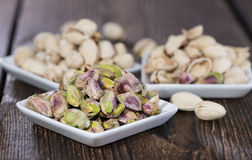 Pistachios in a bowl (on wood) Stock Images