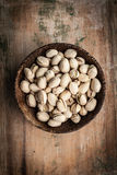 Pistachios. In a bowl on a wooden surface stock image