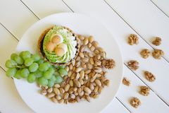 Pistachios, a bunch of grapes, cake and walnuts on white boards. Country breakfast royalty free stock photos