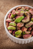 Pistachios in ceramic jar. Pistachios in white ceramic jar on rustic fabric background Stock Images