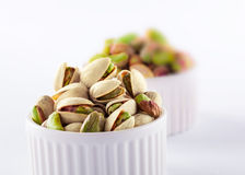 Pistachios in ceramic jars. On white background Stock Photography