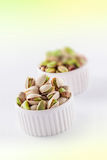Pistachios in ceramic jars. On white and green background Royalty Free Stock Image