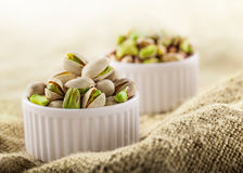 Pistachios in ceramic jars. On white and rustic fabric background Royalty Free Stock Photo