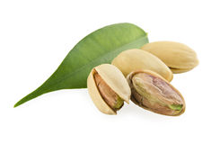Pistachios and a green leaf. On a white background Stock Photography