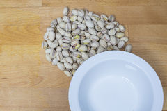 Pistachios lying on a wooden background beside a white bowl Royalty Free Stock Photo