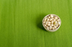 Pistachios Nuts on green Table cloth background Stock Photo