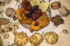 Pistachios,nuts,hazelnuts near a crystal rosette with dried fruit,eclairs,cinnamon on a figured napkin. Pistachios,nuts,hazelnuts near a crystal rosette with Stock Image