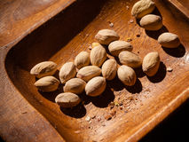 Pistachios nuts in wooden bowl. Unhealthy food. Stock Photos