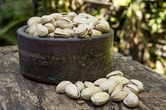 Pistachios. Pin pistachios in ceramic bowl on wooden table Stock Photos