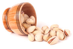 Pistachios pouring out of wooden bowl  on white background Stock Photo