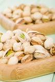 Pistachios. Roasted and salted pistachio nuts in a bamboo bowl Stock Photos