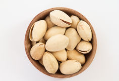 Pistachios in a round wooden form. On a white background Royalty Free Stock Image