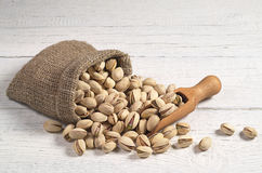 Pistachios in sack. Pistachios nuts in sack and near on white wooden table Stock Image
