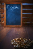 Pistachios in a scoop on a brown wooden floor. Blank black board space for text. Royalty Free Stock Photo